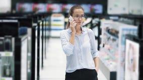 Красивые телефонный звонок и беседы ответов девушки в косметическом магазине, замедленном движении сток-видео