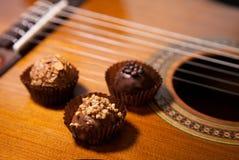 Красивые трюфеля на предпосылке гитары Стоковое фото RF