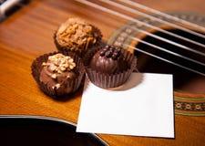 Красивые трюфеля на предпосылке гитары Стоковые Фото