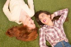 Красивые туристские дамы лежа на зеленой траве Стоковое фото RF