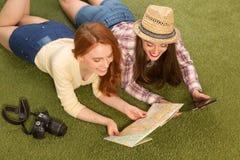 Красивые туристские дамы лежа на зеленой траве Стоковые Фотографии RF