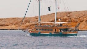 Красивые туристские ветрила яхты в бурном море на предпосылке утесов E видеоматериал
