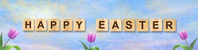 Красивые тюльпаны на солнечном облачном небе Счастливая пасха, надпись на деревянных блоках Предпосылка пасхи стоковая фотография rf