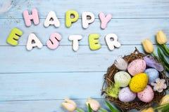 Красивые тюльпаны e с красочными яичками в гнезде на голубых деревянных предпосылке и печеньях помечая буквами счастливую пасху Стоковые Изображения