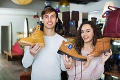 Красивые усмехаясь ботинки зимы молодых пар покупая Стоковые Фото