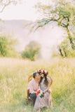 Красивые усмехаясь молодые пары сидя в стуле совместно лицом к лицу Стоковая Фотография
