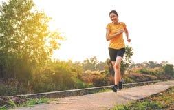 Красивые усмехаясь тайские женщины, который побежали и jogging на следе п стоковое изображение