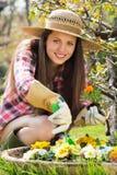 Красивые улыбки молодой женщины с цветком в руке стоковые фотографии rf