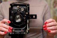 Красивые хорошо выхоленные женские руки принимают фото на старой камере стоковые фото