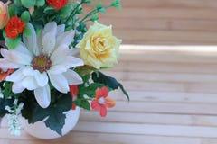 Красивые цветки в вазе на деревянной коричневой предпосылке Стоковое Изображение