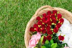 Красивые цветки в плетеной корзине на поле зеленой травы (красный цвет, Стоковые Фото