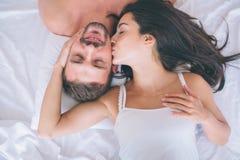 Красивые человек и женщина лежат в белой кровати Гай держит глаза закрытый и усмехается Девушка касается его щеке и целовать стоковые изображения rf