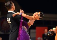 Красивые человек и женщина в фиолетовом платье выполняют усмехаться во время конкуренции dancesport Стоковое Изображение