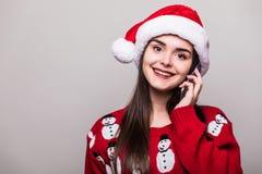 Красивые шляпа santa носки модели девушки и свитер рождества говорят на телефоне Стоковые Фотографии RF