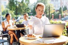 Красивые электронные почты чтения женщины пока выпивающ кофе Стоковое Изображение
