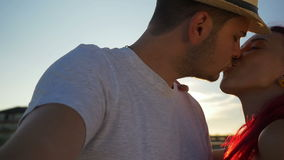 Красивые любовники целуя и снимая на пляже на заходе солнца сток-видео