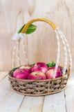 Красивые яблоки в плетеной корзине на деревянной предпосылке Стоковое Фото