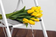 Красивые яркие желтые тюльпаны более лежа на лестницах белизны софы Стоковые Фотографии RF