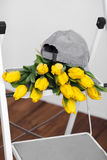 Красивые яркие желтые тюльпаны более лежа на лестницах белизны софы Стоковые Фото