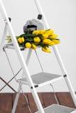Красивые яркие желтые тюльпаны более лежа на лестницах белизны софы Стоковые Изображения