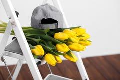 Красивые яркие желтые тюльпаны более лежа на лестницах белизны софы Стоковая Фотография