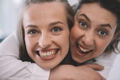 Красивые excited гомосексуальные пары обнимая и усмехаясь стоковое изображение