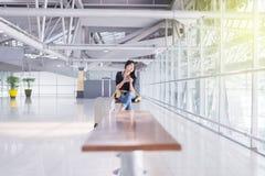Красивый азиатский путешественник женщины используя мобильный телефон в авиапорте, образ жизни используя сотовый телефон Стоковые Изображения