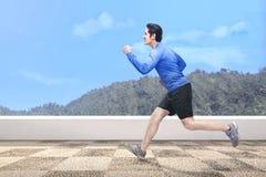 Красивый азиатский человек бежать outdoors Стоковое фото RF