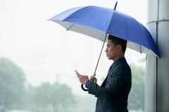 Красивый азиатский человек используя Smartphone в дожде Стоковое Фото