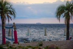 Красивый ландшафт захода солнца с курсируя шлюпкой на пляже океана тропическом с sardegna Италией ладоней стоковая фотография rf