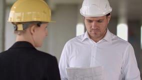 Красивый архитектор с заведущей места выставки строительной площадки строения вверх на строительной площадке акции видеоматериалы