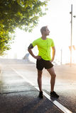 Красивый атлетический человек принимая пролом после бежать снаружи в парке пока смотрящ прочь Стоковые Изображения RF