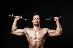 Красивый атлетический человек при гантели уверенно смотря вперед стоковые фото