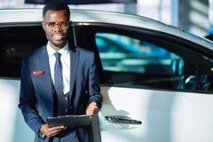 Красивый африканский продавец автомобилей стоя на дилерских полномочиях держа таблетку стоковое фото rf