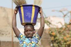 Красивый африканский ребенок помогая ее семье - символу детского труда Стоковые Изображения