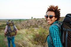 Красивый африканский усмехаться девушки, смотря камеру, предпосылка путешественника друга Стоковые Изображения