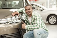 Красивый африканский человек выбирая новый автомобиль на дилерских полномочиях стоковые изображения rf