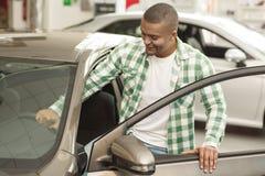 Красивый африканский человек выбирая новый автомобиль на дилерских полномочиях стоковое изображение