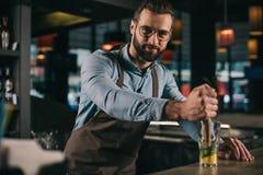 красивый бармен подготавливая питье и смотреть спирта стоковые изображения