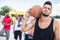 Красивый баскетболист с шариком на плече стоя на суде Стоковые Изображения RF