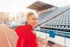 Красивый бегун дамы в теплых одеждах на стадионе смотря в сторону Нося красный клобук Вскользь концепция носки спорта Стоковая Фотография RF