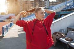Красивый бегун дамы в теплых одеждах на стадионе смотря в сторону Нося красный клобук Вскользь концепция носки спорта Стоковые Изображения