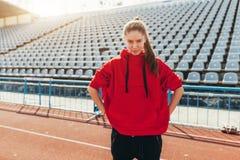 Красивый бегун дамы в теплых одеждах на стадионе смотря в сторону Нося красный клобук Вскользь концепция носки спорта Стоковые Фото