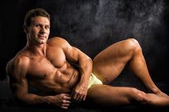 Красивый без рубашки мышечный человек кладя вниз на пол в купальном костюме стоковая фотография