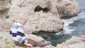 Красивый белокурый мальчик бросает камни на море акции видеоматериалы