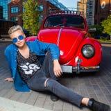 Красивый белокурый молодой человек в голубых солнечных очках, сидя перед стоковое фото