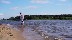 Красивый белый человек в скольжениях футболки на доске воды на крае влажного пляжа песка видеоматериал
