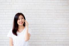 Красивый беседы женщины портрета телефона и улыбки молодой азиатской умного стоя на предпосылке кирпича цемента Стоковое Изображение