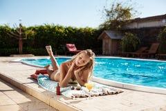 Красивый белокурый загорать девушки, лежа около бассейна Стоковое Изображение