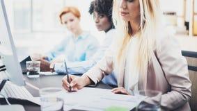 Красивый белокурый документ подписания женщины на рабочем месте в офисе Группа в составе сотрудники девушек обсуждая совместно пр Стоковые Изображения RF